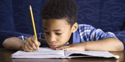 An African-American boy does his homework forlornly