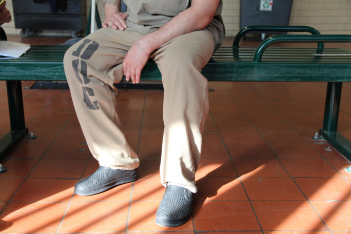 An inmate at Cook County Jail is shown from the waist down, sitting in his khaki uniform