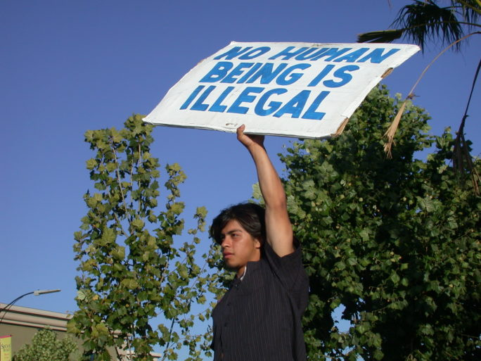 "A man holds a sign reading ""No human being is illegal"""